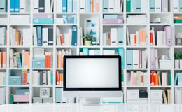 Professional workspace with computer and shelves. Professional creative workspace with computer on a white desktop and colorful folders on the shelves Stock Photo