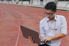 Professional young Asian businessman with laptop standing on race track. business vision concept. stock image