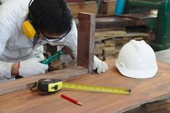 Professional young Asian carpenter with safety uniform holding hammer with other tools in carpentry workshop. Professional young Asian carpenter with safety royalty free stock photos