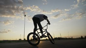 Professional young bicycler jumping on his bike rotating the handlebar in midair exercising ollie trick  at sunset  -. Professional young bicycler jumping on his stock footage