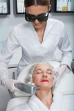 Professional young cosmetician is undergoing laser therapy Stock Photos