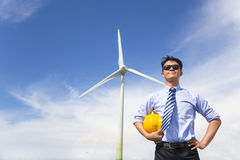 Professional young engineer standing with wind generator Stock Images