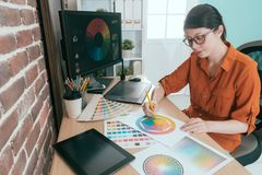 Professional young female graphic designer. Choosing design color in office royalty free stock photo