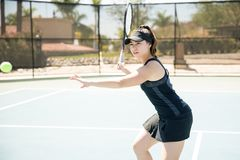 Tennis player in action. Professional young hispanic female tennis player preparing to make forehand shot on court during a match Royalty Free Stock Photo