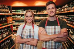Professional young man and woman stand in grocery store and pose on camera. She hold hands crossed and smile. Happy. Positive workers wear apron stock photo