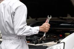 Professional young mechanic man in uniform with wrench diagnosing engine against open hood at the repair garage. Car insurance con Stock Photos