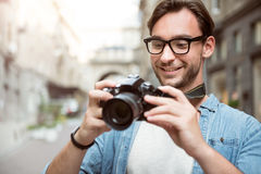 Professional young photographer holding his camera. Urban photoshoot. Pleasant good looking joyful photographer holding his camera and smiling while looking at Stock Photography