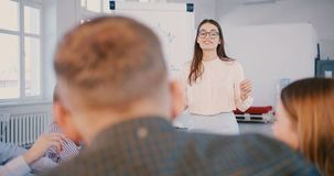 Professional young positive business expert woman in glasses speaking to happy multiethnic team at training seminar. stock footage