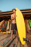 Professional young surfer getting board ready for surf. At the beach and looking away Stock Image