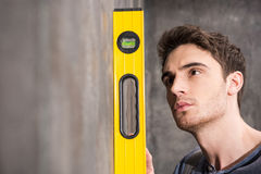 Professional young worker measuring wall with level tool Royalty Free Stock Image