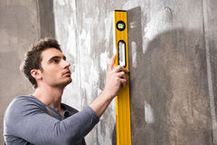 Professional young worker measuring wall with level tool Stock Photos