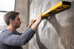 Professional young worker measuring wall with level tool Stock Image