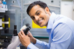 Professionalism. Closeup portrait, young friendly scientist looking into microscope. Isolated lab background. Research and development sector royalty free stock photo