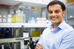 Professionalism. Closeup portrait, young friendly scientist standing by microscope.  lab background. Research and development sector Royalty Free Stock Photography