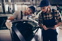 Professionalism, maintenance. Two busy expert engineers at mechanical work shop, in special safety outfit uniform, protective. Spectacles, focused, serious royalty free stock photography
