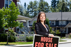Professionally dressed real estate woman outside with a sign. Professionally dressed real estate woman outside in a neighborhood leaning on a for sale sign Royalty Free Stock Image