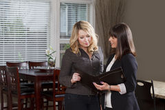 Professionally dressed women look over information inside a hous Royalty Free Stock Images