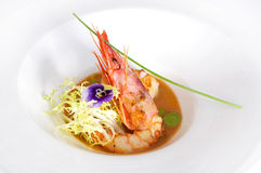 Professionally prepared food with cooked shrimp. Sauce, salad a violet flower royalty free stock photography