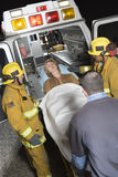 Professionals Carrying Patient On Stretcher In Ambulance. Emergency service professionals carrying patient on stretcher in ambulance Royalty Free Stock Photo
