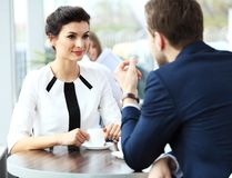Professionals chatting during a coffee break. Young couple of professionals chatting during a coffee break royalty free stock photo