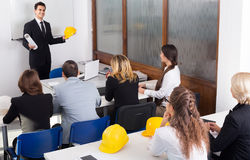 Professionals and coach at design training Stock Images