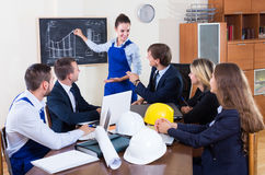 Professionals  having meeting indoors. Caucasian professionals with helmets and laptops having meeting indoors Royalty Free Stock Image