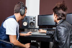 Professionals Mixing Audio Together In Recording. Young men and female professionals mixing audio together in recording studio Stock Photos