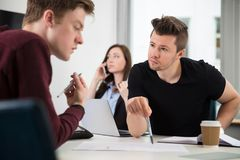 Professionals Planning While Colleague Using Smart Phone In Offi. Serious male professionals planning while female colleague using smart phone in office Royalty Free Stock Photo