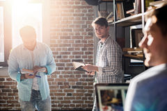 Professionals working on new business project with laptop and books in small business office Stock Photos