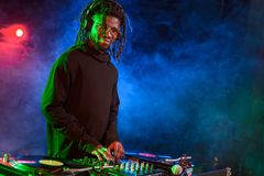 professioneel Afrikaans Amerikaans DJ in hoofdtelefoons met correcte mixer stock fotografie