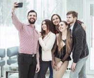 Professioneel commercieel team die selfie terwijl status dichtbij venster in bureau maken royalty-vrije stock foto's