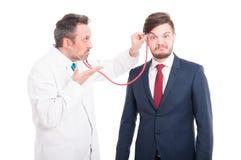 Professioneel dokters cheking hoofd van krankzinnige advocaat stock afbeeldingen