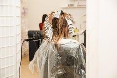 Professioneel herenkapper scherp haar van vrouwelijke cliënt Hoofdstilist die haarkleur en hoogtepunten toepassen Blondevrouw met royalty-vrije stock afbeeldingen