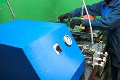 Professioneel industrieel materiaal, post voor het belasten van brandblusapparaten met drukmaten en slangen in de workshop stock afbeeldingen