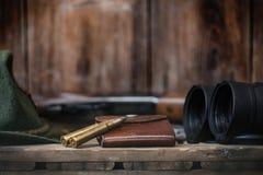 Professioneel jagersmateriaal om te jagen Detail op de munitie De houten zwarte achtergrond met geweer, de hoed, en andere equipm Stock Afbeeldingen