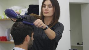 Professioneel kapper drogend haar in schoonheidssalon Mannelijke jonge klant en vrouwelijke kapper Sluit omhoog stock video