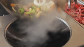 Professioneel kok bradend groenten en vlees bij het festival van het straatvoedsel Beweeg gebraden gerecht met rundvlees en groen stock video