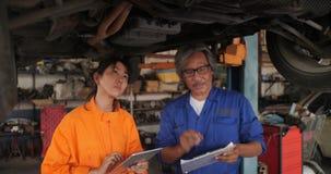 Professioneel mechanisch team die digitale tablet gebruiken terwijl het werken onder opgeheven auto stock videobeelden