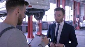 Professioneel onderhoud en mensen, werktuigkundige met klembord en klant of autoeigenaar op workshop stock footage