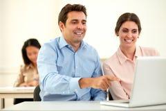 Professioneel paar die bij laptop en het glimlachen werken stock foto's
