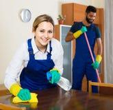 Professioneel paar in het eenvormige schoonmaken bij binnenlands binnenland royalty-vrije stock foto's