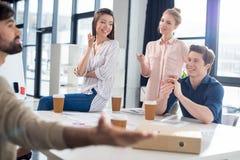 Professioneel zakenlui die koffie drinken terwijl het bespreken en brainstorming in kleine bedrijfsbureau royalty-vrije stock fotografie