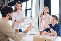 Professioneel zakenlui die koffie drinken terwijl het bespreken en brainstorming in kleine bedrijfsbureau stock afbeeldingen