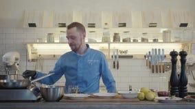 Professioneel zeker chef-kokkooktoestel in zwarte handschoenen friyng of het stoven plakken van courgette en graan op een hete pa stock videobeelden