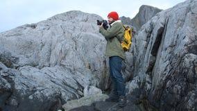 Professionele aardfotograaf met camera op de bovenkant van de berg die rond en beelden neemt eruit ziet stock videobeelden
