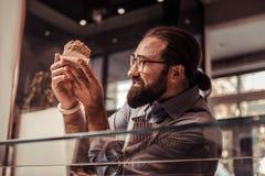 Professionele aardige bakker die de gebakjecake bekijken royalty-vrije stock afbeelding