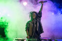 professionele Afrikaanse Amerikaanse club DJ in hoofdtelefoons met correcte mixer en microfoon royalty-vrije stock foto