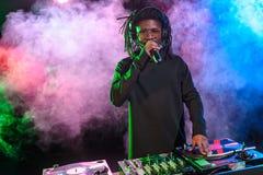 professionele Afrikaanse Amerikaanse club DJ met correcte mixer en microfoon stock afbeelding