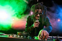 professionele Afrikaanse Amerikaanse club DJ met microfoon en correcte mixer stock foto's