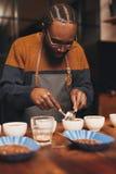Professionele Afrikaanse barista die perfecte kop van cof opleiden te maken royalty-vrije stock fotografie